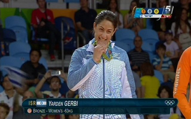Israeli judoka Yarden Gerbi playfully bites her bronze medal for the women's under-63kg category during the awards ceremony at the Olympic Games in Rio on August 9, 2016 (screen capture: Channel 55)