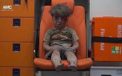 In this frame grab taken from video provided by the Syrian anti-government activist group Aleppo Media Center (AMC), 5-year-old Omran Daqneesh sits in an ambulance after being pulled out or a building hit by an airstirke, in Aleppo, Syria, Wednesday, Aug. 17, 2016. (Aleppo Media Center via AP)
