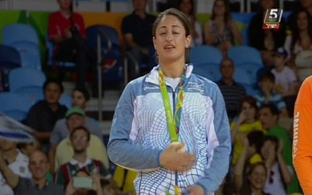 Israeli judoka Yarden Gerbi clutches her bronze medal for the women's under-63kg category during the awards ceremony at the Olympic Games in Rio on August 9, 2016 (screen capture: Channel 55)