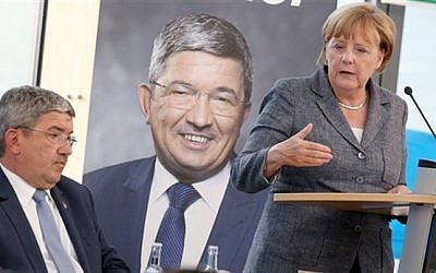 German Chancellor Angela Merkel speaks alongside Lorenz Caffier, left, of Merkel's Christian Democrats, during an election campaign in Neustrelitz, Germany on Aug. 17, 2016. (Bernd Wuestneck/dpa via AP)