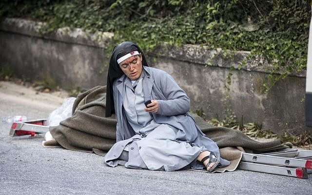 A nun checks her mobile phone as she lies near a victim laid on a ladder following an earthquake in Amatrice Italy, August 24, 2016. (Massimo Percossi/ANSA via AP)