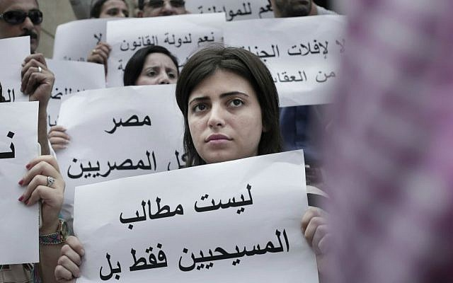 "An Egyptian woman holds a sign in Arabic that reads, ""the demands are not only for Christians but for all Egyptians,"" during a protest against the latest surge of assaults on Christians in Cairo, Egypt, Saturday, Aug. 13, 2016. (AP Photo/Nariman El-Mofty)"