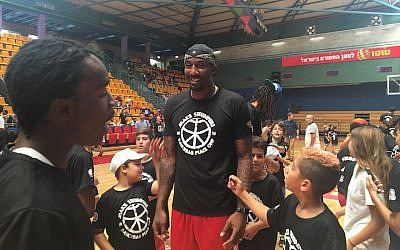 Amar'e Stoudemire is surrounded by young fans at his youth basketball camp in Jerusalem, August 8, 2016. (Andrew Tobin)