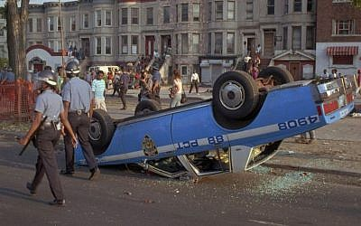 In this Aug. 21, 1991 file photo, New York City Police Department officers, in riot gear, walk past a police car that was overturned by rioters in the Crown Heights section of the Brooklyn borough of New York.  (AP/David Burns)