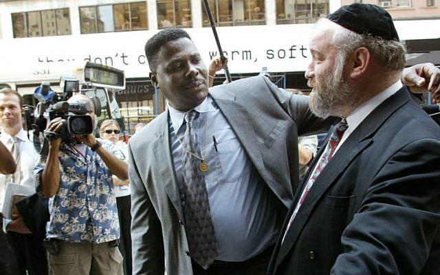 File: In this Aug. 19, 2002, file photo, Carmel Cato, center, reaches out to embrace Norman Rosenbaum, right, as they walk together in a show of unity into a New York restaurant on the 11th anniversary of the 1991 Crown Heights riots sparked by the deaths of Cato's 7-year-old son Gavin Cato and the murder of Rosenbaum's brother Yankel, an Australian doctoral student. On Sunday, Aug. 21, 2016, residents of the Crown Heights neighborhood in Brooklyn mark the 25th anniversary of the riot. (AP Photo/Beth A. Keiser, File)