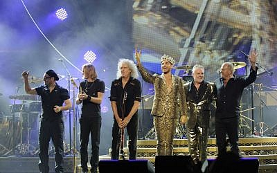 Members of the band Queen with Adam Lambert (in gold lame), standing in for the beloved and deceased Freddie Mercury (Courtesy Queen)