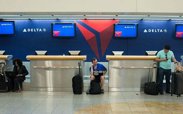 Passengers wait at the Delta ticket counter at Hartsfield–Jackson Atlanta International Airport, Monday, Aug. 8, 2016, in Atlanta, Georgia. (AP Photo/Branden Camp)