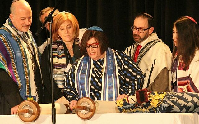 Rabbi Denise Eger, a contributor to 'The Sacred Calling,' center, reading Torah during her installation as CCAR president, March 16, 2015. (David A.M. Wilensky)