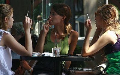 Israeli women smoke cigarettes while spending time at a cafe in central Tel Aviv. (Kobi Gideon / FLASH90)