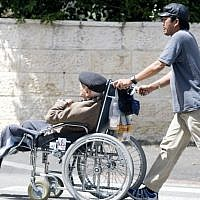 Illustrative: A Filipino caregiver walks with an Israeli man sitting in a wheelchair on April 22, 2009. (Abir Sultan/Flash90)