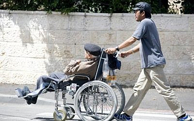 Illustrative: A Filipino caregiver walks with an elderly Israeli man sitting in a wheelchair on April 22, 2009. (Abir Sultan/Flash90)