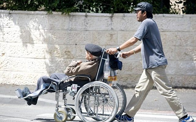 Illustrative: A Filipino caregiver walks with an Israeli man sitting in a wheelchair on April 22, 2009. (Abir Sultan/Flash90)
