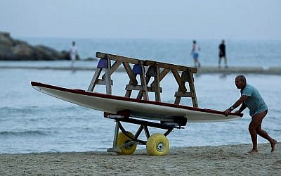 Illustrative: A Lifeguard pushing his boat at Tel Aviv Beach. (Moshe Shai/Flash90)