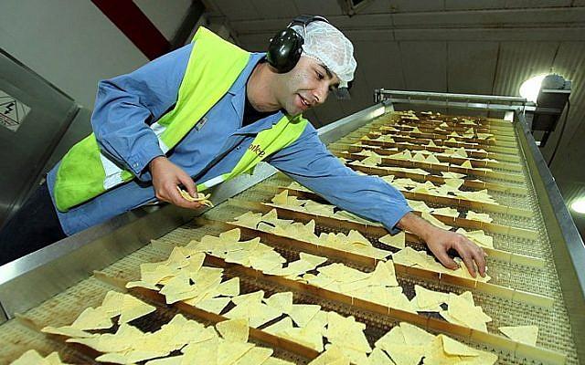 ILLUSTRATIVE PHOTO. An Israeli laborer working at a potato chip factory in Israel. (Moshe Shai/FLASH90)