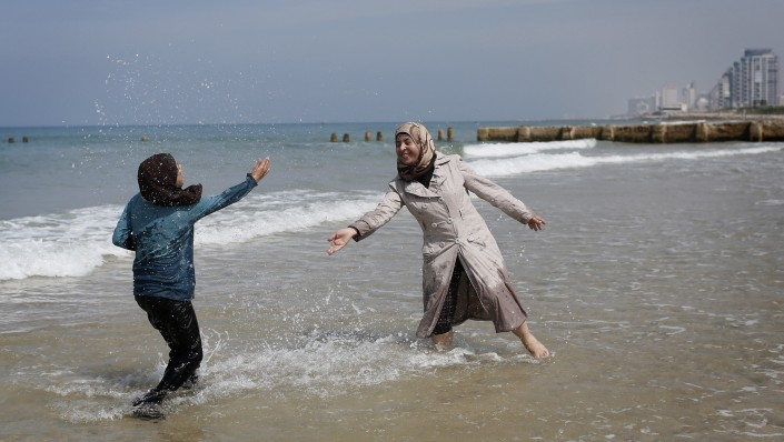 Young Palestinian women from the West Bank town of Bethlehem play on the beach in Tel Aviv on March 23, 2014. (Miriam Alster/Flash90)