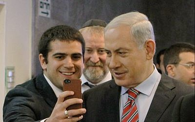 Prime Minister Benjamin Netanyahu poses for a selfie with student on March 30, 2014 (Danny Meron/POOL/Flash90)