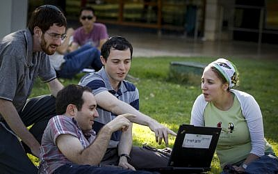 Students sitting on the grass at Hebrew University of Jerusalem's Givat Ram campus on October 27, 2014. (Miriam Alster/Flash90)