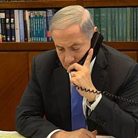 Prime Minister Benjamin Netanyahu speaking on the phone at the Prime Minister's Office in Jerusalem, April 28, 2014. (Amos Ben Gershon/GPO)