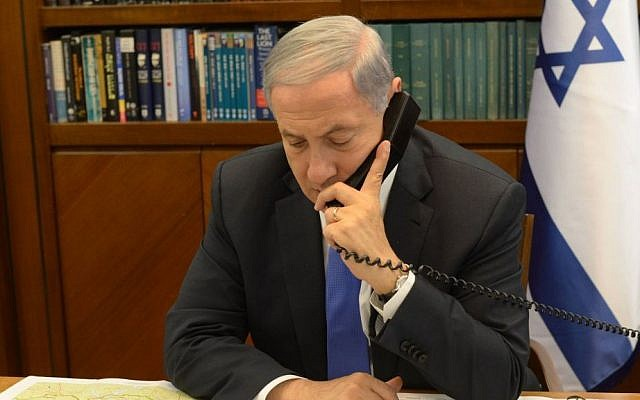 Illustrative: Prime Minister Benjamin Netanyahu speaking on the phone at the Prime Minister's Office in Jerusalem, April 28, 2014. (Amos Ben Gershon/GPO)