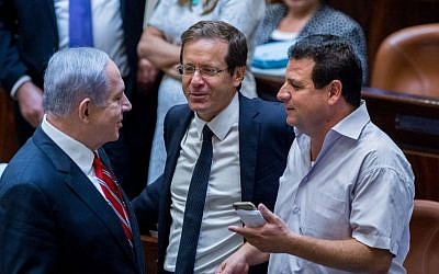 In this undated photo, Prime Minister Benjamin Netanyahu (L) speaks with Leader of the Zionist Union party Isaac Herzog (C) and Leader of the Joint (Arab) List, Ayman Odeh in the Knesset. (Yonatan Sindel/Flash90)