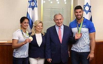 Prime Minister Benjamin Netanyahu and his wife Sara seen with Israeli judokas and Olympic medalists Ori Sasson and Yarden Gerbi during a meeting with sport's delegation to the 2016 Rio Olympics Games, at the Prime Minister's Office in Jerusalem, August 17, 2016. (Amit Shabi/Pool)