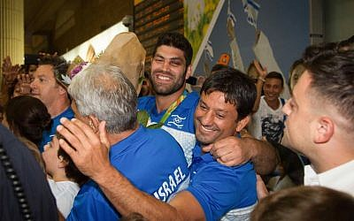 Or Sasson, center, is greeted by supporters at Ben-Gurion Airport on August 15, 2016. (Roy Alima/Flash90)