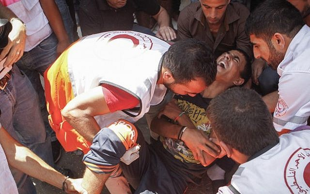 A wounded Palestinian is evacuated by medical staff during clashes with Israeli soldiers in the al-Fawar refugee camp on August 16 2016. (Wisam Hashlamoun/Flash90)