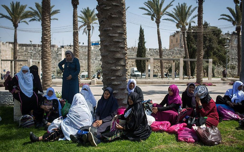 Arab women wait in the shade outside the walls of the Muslim Quarter of Jerusalem's Old City, on August 22, 2016. (Photo by Hadas Parush/Flash90)
