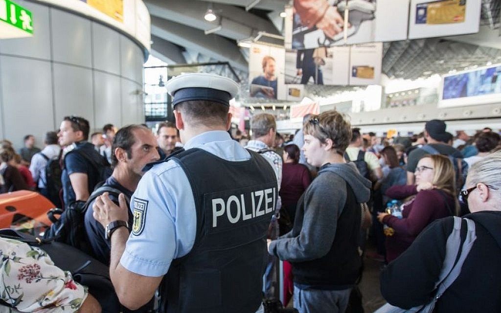Illustrative: A policeman talks to travelers in the departure area at Frankfurt airport, central Germany (Frank Rumpenhorst/dpa via AP)