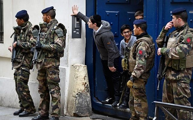Children peering out from a doorway as armed soldiers patrol outside their school in the Jewish quarter of the Marais district in Paris, France, January 13, 2015. (Jeff J Mitchell/Getty Images/via JTA)