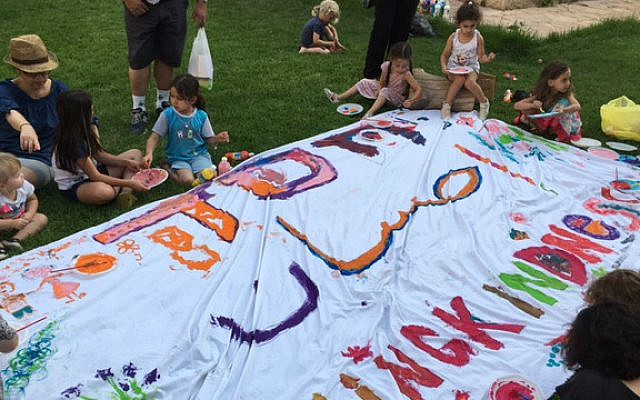 Working on a giant banner of loving kindness, at the back-to-school celebration in Jerusalem's YMCA on Monday, August 29 (Courtesy Dasee Berkowitz)