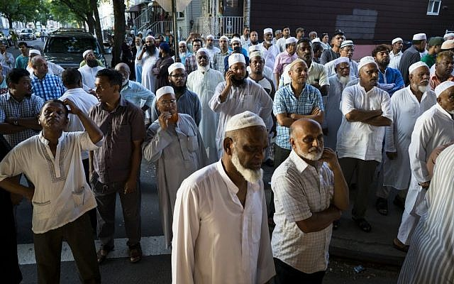 People gather near a crime scene for a demonstration after the leader of a New York City mosque and an associate were fatally shot in a brazen daylight attack as they left afternoon prayers August 13, 2016. Police said 55-year-old Imam Maulama Akonjee and his 64-year-old associate, Tharam Uddin, were shot in the back of the head as they left the Al-Furqan Jame Masjid mosque in the Ozone Park section of Queens shortly before 2 p.m. (AP Photo/Craig Ruttle)