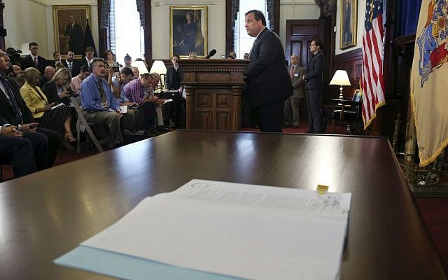 New Jersey Gov. Chris Christie addresses a gathering after signing legislation at the Statehouse that would bar the state's public pension fund from investing with companies that boycott Israel or Israeli businesses, Tuesday, Aug. 16, 2016, in Trenton, New Jersey. (AP Photo/Mel Evans)