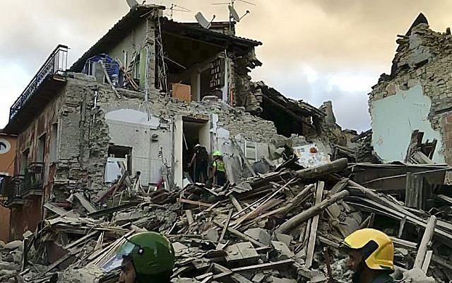 Still image taken from video shows rescuers searching a collapsed building in Amatrice, central Italy, where a 6.1 earthquake struck just after 3:30 a.m., August 24, 2016. (AP Photo)