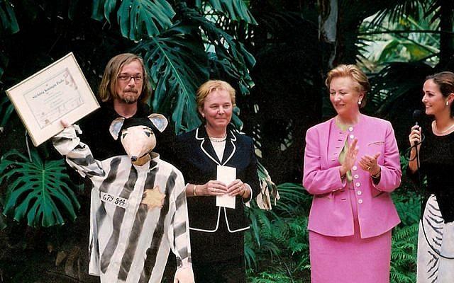 Luc Descheemaeker (back row, left) receiving an award from Belgium's Queen Paola (in pink), in 2002 for his children's puppet theater play based on Art Spiegelman's cartoon Holocaust memoir 'Maus.' (Courtesy of Sint-Jozefs Institute/JTA)