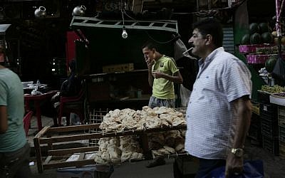 In this Wednesday, Aug. 9, 2016 photo, an Egyptian boy tries to sell bread at a market in downtown Cairo, Egypt. (AP Photo/Nariman El-Mofty)