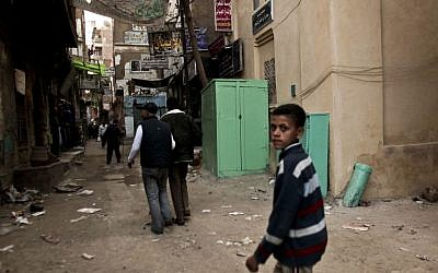Residents pass a kiosk, center, that is used as a clinic where girls are circumcised by a barber, in the Imbaba area of Giza, Egypt, Novenbe 26, 2012. (AP/Maya Alleruzzo, File)