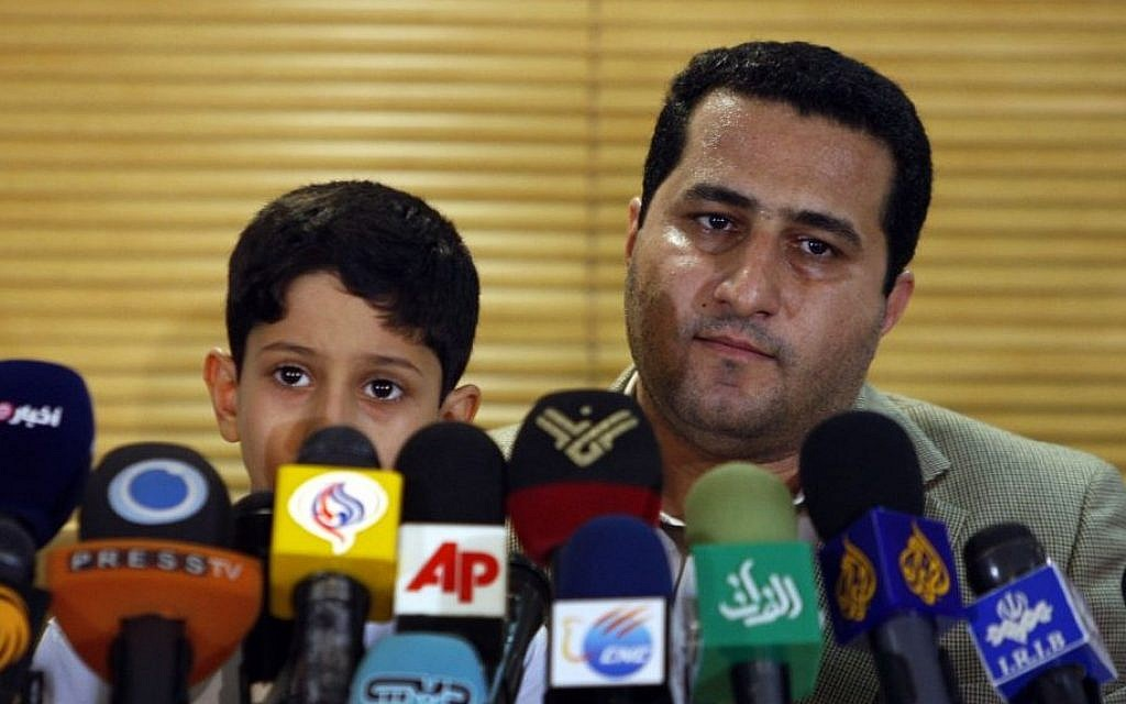 Shahram Amiri, an Iranian nuclear scientist attends a news briefing while holding his son Amir Hossein as he arrives at the Imam Khomeini airport just outside Tehran, Iran, after returning from the United States on July 15, 2010. (AP/Vahid Salemi)