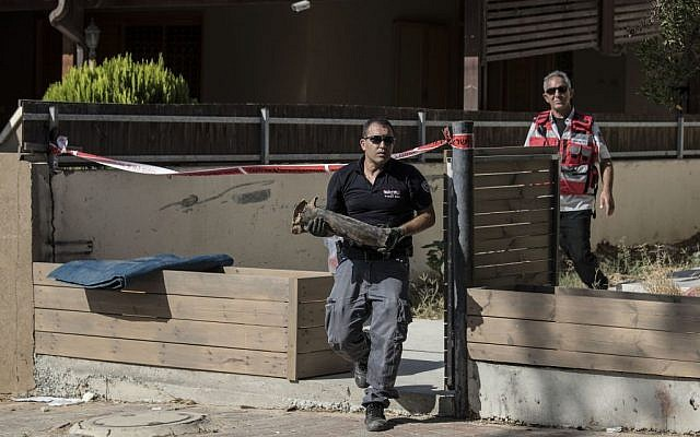 An Israeli police sapper carries part of a rocket which landed in a yard of a house in the city of Sderot, southern Israel, Sunday, August 21, 2016. (AP/Tsafrir Abayov)