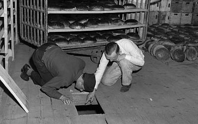 US Lt. Robert R, Rogers, left, and Erich Pinkau, of the German criminal police, examine the under-floor hiding place where arsenic was found in a Nuremberg, Germany bakery which supplied bread to Stalag 13, April 1946. (US Army Signal Corps via AP)
