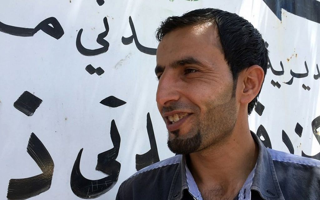 Sabri Mashaaleh, 29, stands in the center of the town of Dhiban, Jordan on July 18, 2016, where he and other unemployed young men had pitched a protest tent over the summer, staging daily protests and demanding jobs before troops dispersed them by force. (AP Photo/Karin Laub)