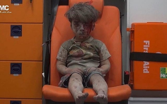 In this frame grab taken from video provided by the Syrian anti-government activist group Aleppo Media Center (AMC), a child sits in an ambulance after being pulled out or a building hit by an airstirke, in Aleppo, Syria, Wednesday, Aug. 17, 2016. (Aleppo Media Center via AP)