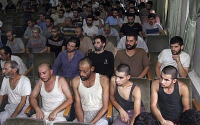 In this Saturday, Sept. 1, 2012, file photo, Syrian prisoners sit in a courtroom before their release in Damascus, Syria. (AP Photo/Bassem Tellawi, File)
