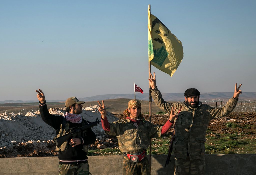 In this Feb. 22, 2015 file photo, Syrian Kurdish militia members of the YPG make a V-sign next to a drawing of Abdullah Ocalan, jailed Kurdish rebel leader, in Esme village in Aleppo province, Syria. (Mursel Coban/Depo Photos via AP)