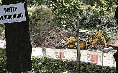 A sign warns against 'trespassing,' as heavy machinery begins the search to find a legendary Nazi train laden with treasure and armaments in Walbrzych, Poland, August 16, 2016. (AP Photo/Dariusz Gdesz)
