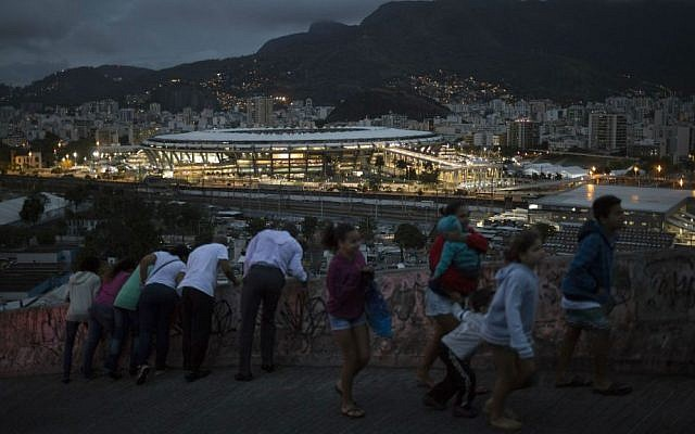 People walk on a viaduct at the Mangueira slum as the Maracana stadium is lit before the closing ceremony of the Summer Olympics in Rio de Janeiro, Brazil, Sunday, Aug. 21, 2016. (AP Photo/Felipe Dana)