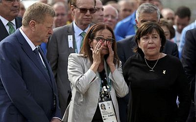 Ilana Romano, center, and Ankie Spitzer, right, widows of Israeli Olympic athletes killed by Palestinian gunmen at the 1972 Munich Olympics, attend a memorial in their husbands' honor, ahead of the Summer Olympics in Rio de Janeiro, Brazil, Wednesday, Aug. 3, 2016. (AP Photo/Edgard Garrido, Pool)