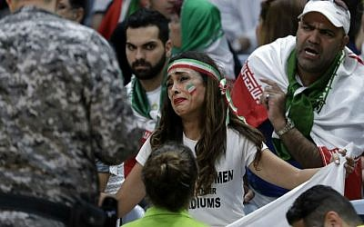 Iranian activist Sarai Darya pleads with Rio Olympics workers and security personnel as they consider removing her for holding up a large sign protesting the fact that women have not been allowed to attend volleyball matches in Iran, during a men's preliminary volleyball match between Egypt and Iran at the 2016 Summer Olympics in Rio de Janeiro, Brazil, Saturday, Aug. 13, 2016. (AP Photo/Jeff Roberson)