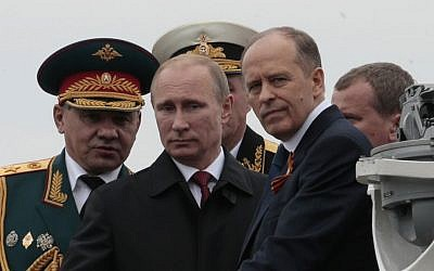 In this file photo taken on Friday, May 9, 2014, Russian President Vladimir Putin, center, flanked by Defense Minister Sergei Shoigu, left, and Federal Security Service Chief Alexander Bortnikov, right, arrives on a boat after inspecting battleships during a navy parade marking Victory Day in Sevastopol, Crimea. (AP Photo/Ivan Sekretarev, File)