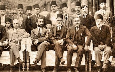 Sir Sassoon Eskell (center, in fez) sits directly on the left of King Faisal I of Iraq (with dark beard) in Baghdad in a photo from the 1920s. (Wikimedia Commons)
